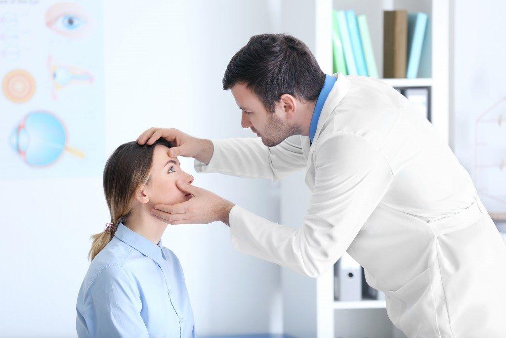 Company doctor examining employee's eyes