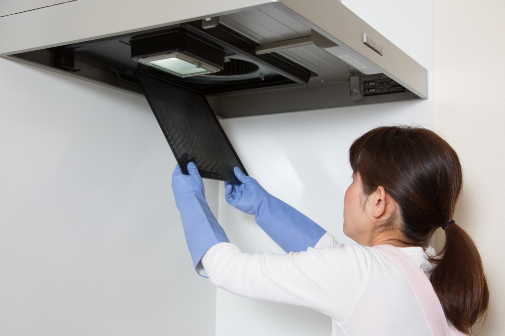 Woman cleaning the AC filter