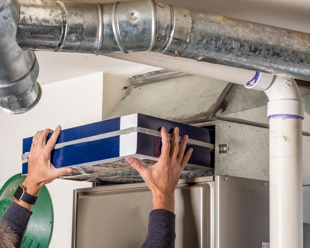 Plumber fixing the furnace filter