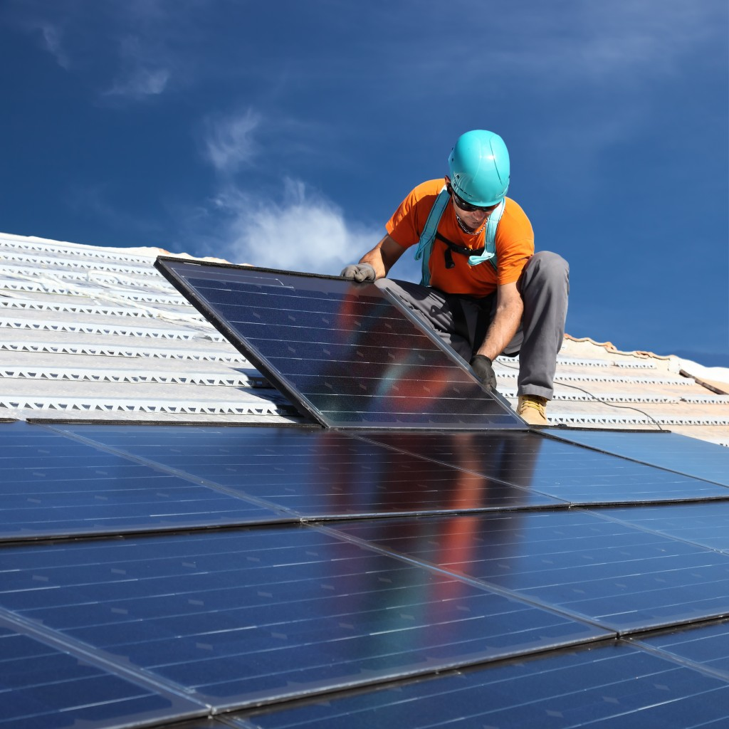 Worker installing solar panels on the roof