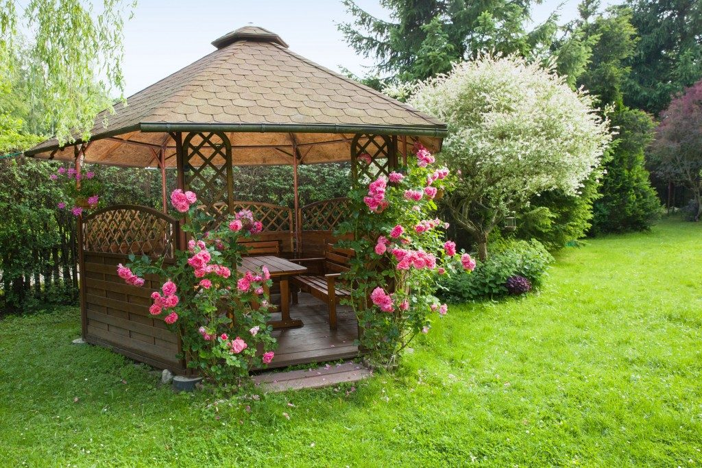 Wooden gazebo with flowers in the backyard