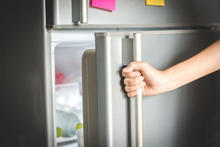 Person opening a gray refrigerator