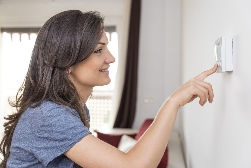 Woman using thermostat