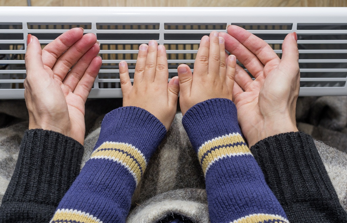 Mother and son using heater