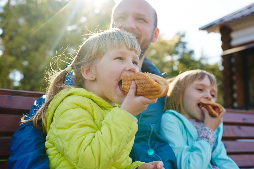 father and her daughters eating hotdog