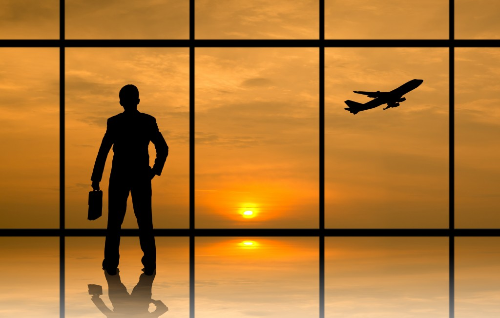 businessman in the airport on his way to his flight overseeing the sunrise