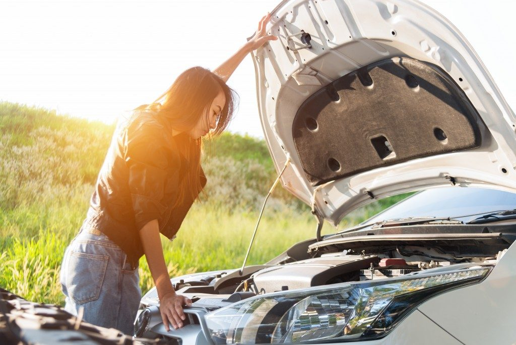 woman checking engine of her car