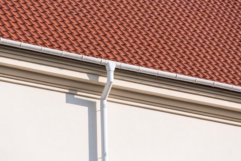 Rain gutter and downspout on the wall of a house