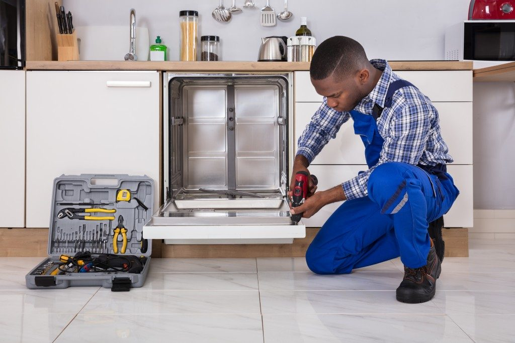 man fixing dishwasher