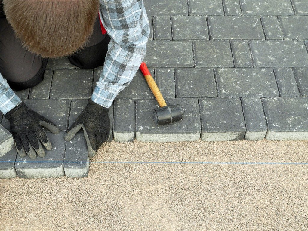 Man fixing the tile for the patio