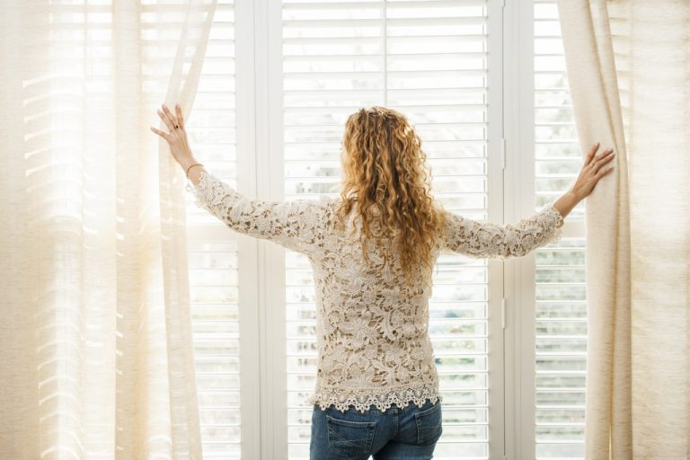 woman opening the curatin over the window blinds