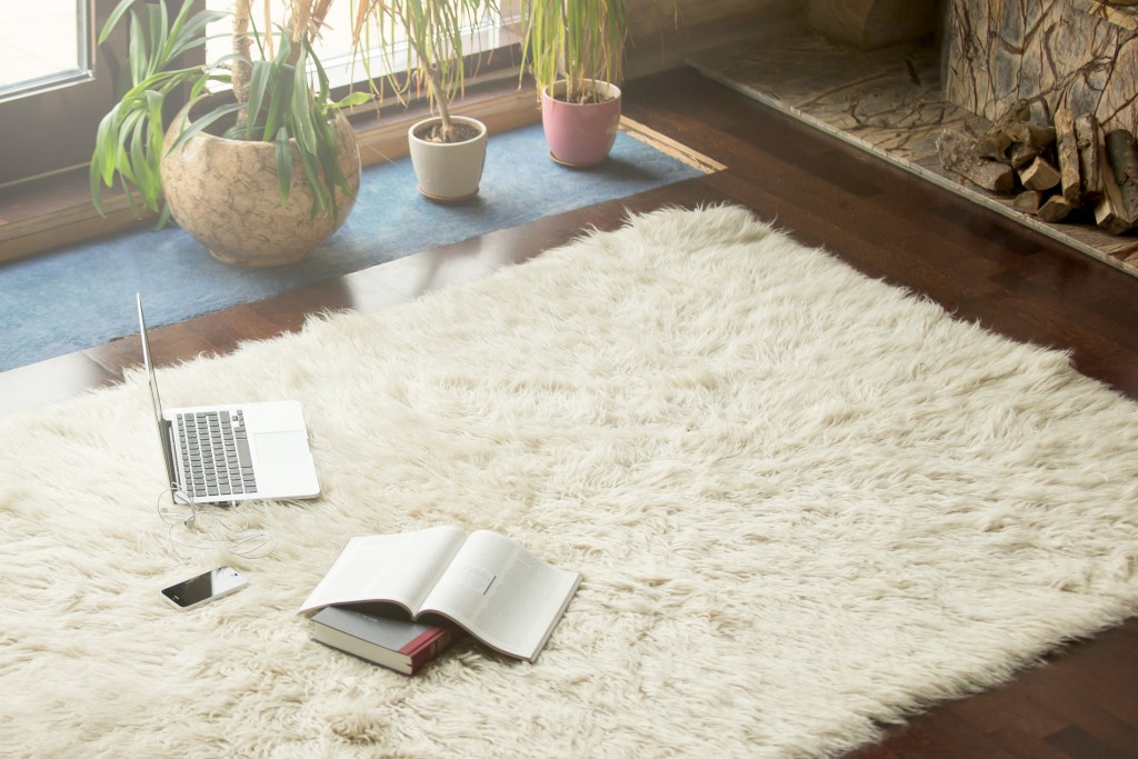 a laptop, phone, and books on top of a white carpet