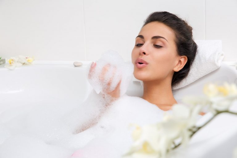 woman blowing bubbles in her bathtub