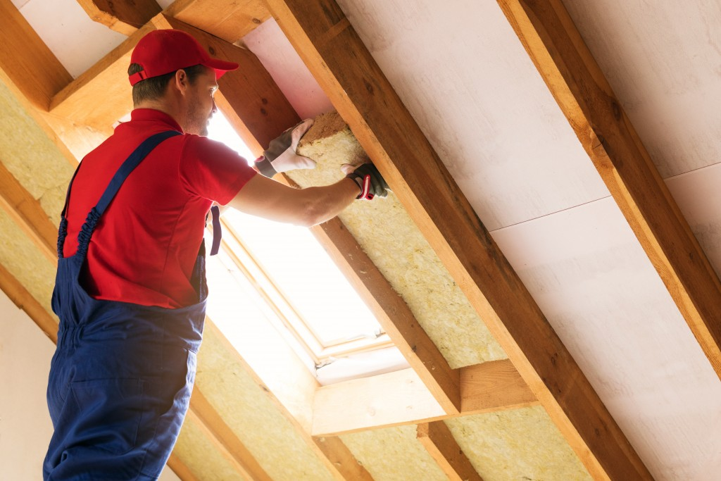 man installing insulation in a home's attic