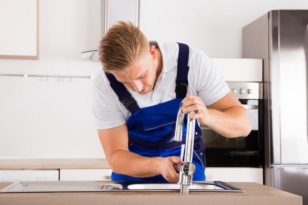 man repairing faucet