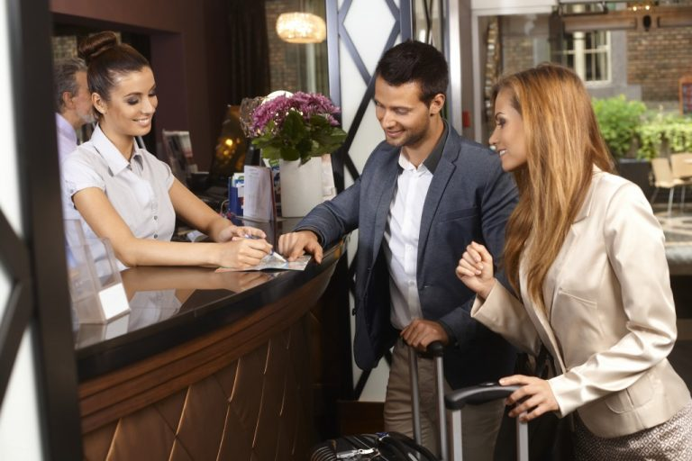 Receptionist giving tourist information to hotel guests upon arrival