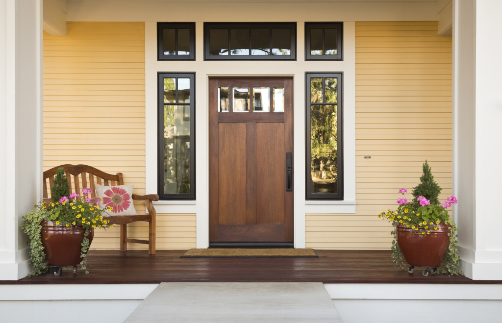Front view of a wooden front door on a yellow house